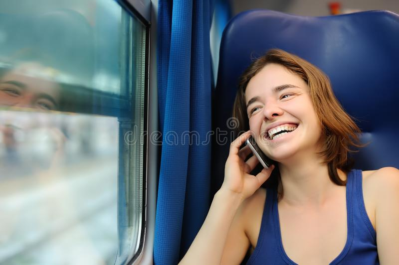 Portrait of a beautiful girl talking on the phone in a train car stock image