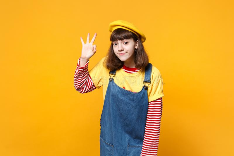 Portrait of beautiful girl teenager in french beret, denim sundress showing OK gesture isolated on yellow wall. Background in studio. People sincere emotions stock photo