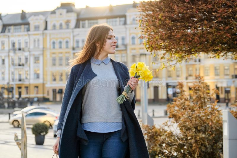 Portrait of beautiful girl walking in city, young woman with bouquet of yellow flowers, background spring city stock photo