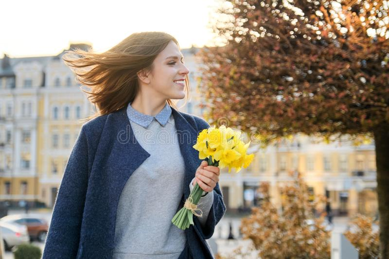 Portrait of beautiful girl walking in city, young woman with bouquet of yellow flowers, background spring city royalty free stock photography