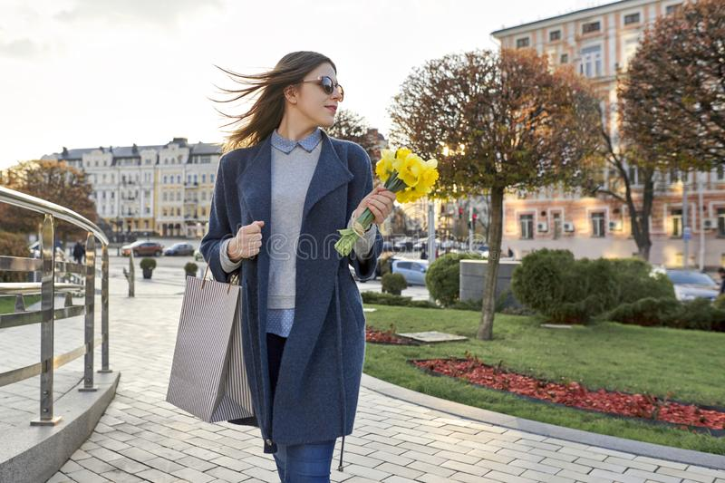 Portrait of beautiful girl walking in city, young woman with bouquet of yellow flowers and shopping bag, background spring city stock photos