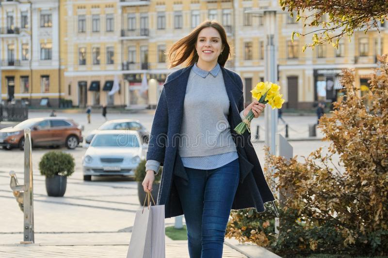 Portrait of beautiful girl walking in city, young woman with bouquet of yellow flowers and shopping bag, background spring city royalty free stock photos