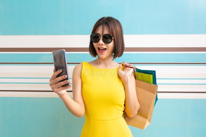 Portrait of beautiful girl wearing dress and sunglasses holding shopping bags royalty free stock photos