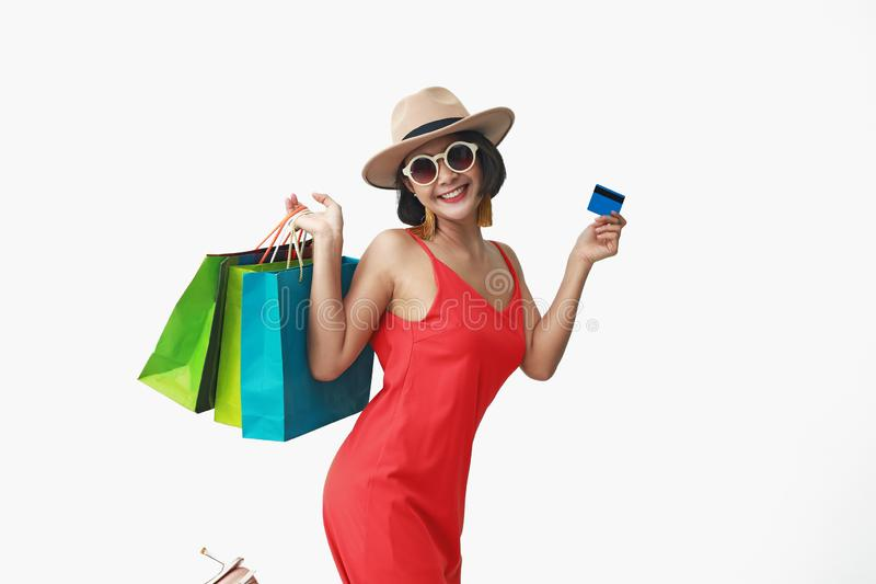 Portrait of beautiful girl wearing dress and sunglasses holding shopping bags stock photography