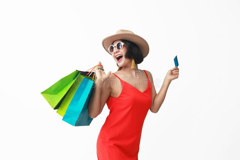 Portrait of beautiful girl wearing dress and sunglasses holding shopping bags royalty free stock image