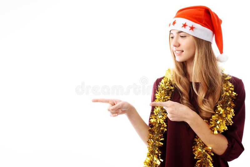 Portrait of a beautiful girl, wearing a Santa Claus hat, points. Her finger into a blank space, isolated on a white background. Christmas stock photography