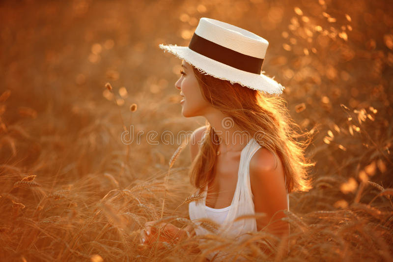Portrait of a beautiful girl in a white dress and hat in the fie. Ld at sunset in summer stock photo