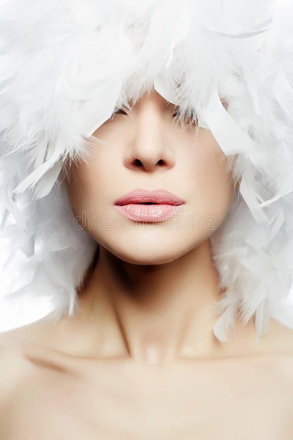 Portrait of Beautiful Girl in white feathers Hat. Young Woman Face, closeup. Beauty Make-up stock photo