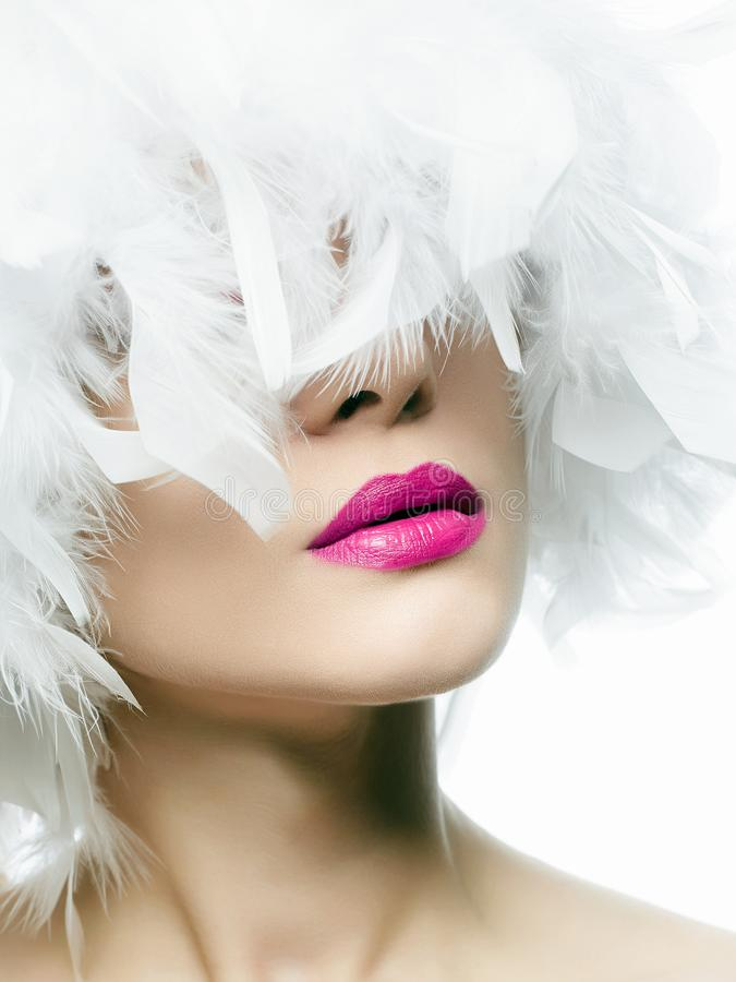 Young woman with pink lips. Portrait of Beautiful Girl in white feathers. young woman with pink lips, beautiful feather hat. Beauty make-up royalty free stock photography