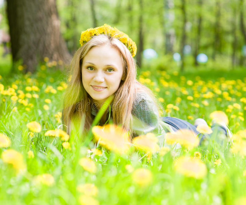 Portrait beautiful girl with a wreath of dandelions lying on the grass stock images