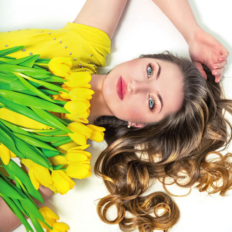 Portrait of beautiful girl with yellow tulips stock photos