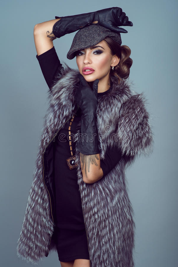 Portrait of a beautiful glam model wearing silver fox jacket royalty free stock photos