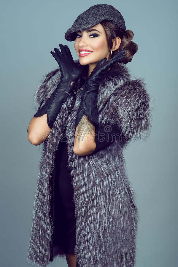 Portrait of a beautiful glam smiling model wearing silver fox jacket royalty free stock image