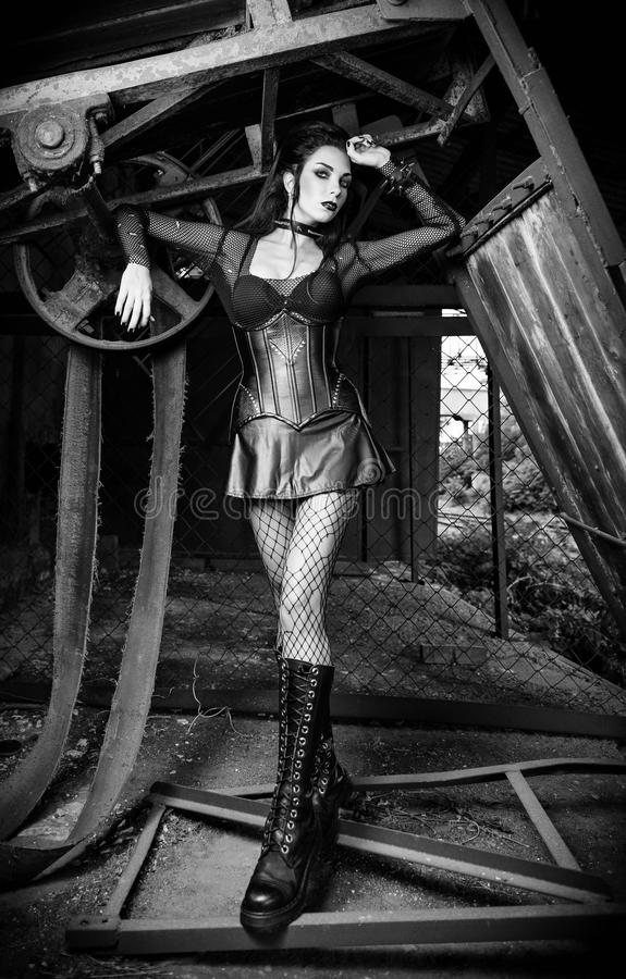 Portrait of beautiful goth deathrock girl dressed in leaky blouse, skirt, corset and boots standing among old mechanisms. Black royalty free stock photo