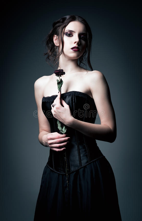 Portrait of beautiful goth girl holding withered flower in hands royalty free stock image