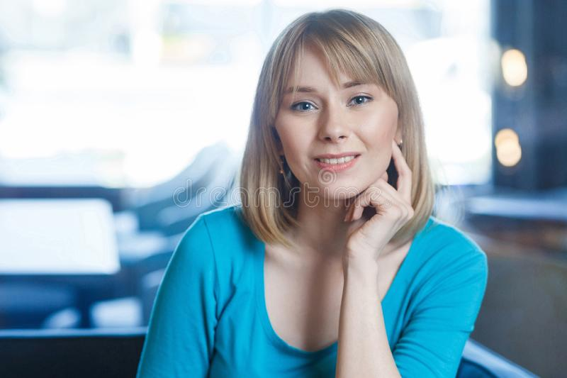 Portrait of beautiful happy attravctive blonde young woman in blue t-shirt with makeup and bangs hair sitting, touching her face stock image