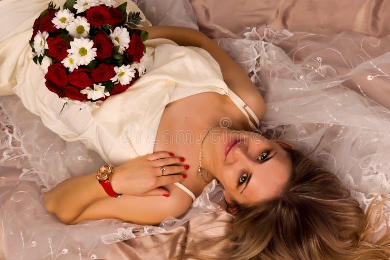 Portrait of a beautiful happy bride lying stock image