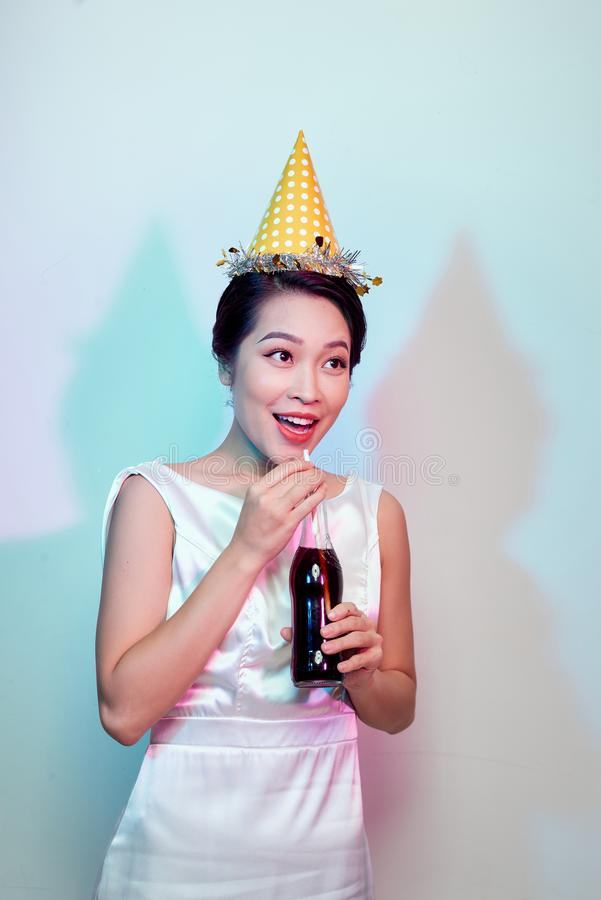 Portrait of beautiful happy cute asian woman in casual dress isolated on white, drinking cola from bottle with straw royalty free stock photos