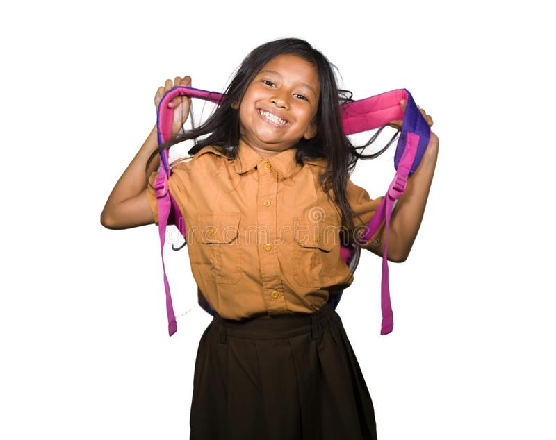 Portrait of beautiful happy and excited female child in school uniform carrying student bag smiling cheerful isolated on white. Background in back to school and stock images