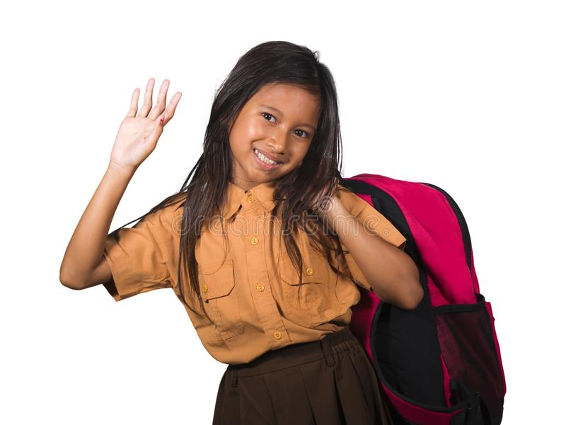 Portrait of beautiful happy and excited female child in school uniform carrying student bag smiling cheerful isolated on white. Background in back to school and stock photography