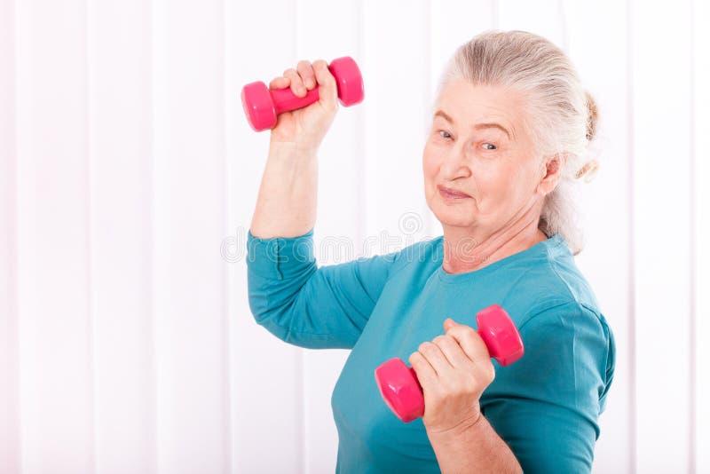 Happy senior woman with dumbbells stock image