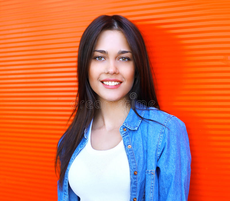 Portrait of beautiful happy smiling brunette woman in jeans. Jacket against the red wall royalty free stock photography