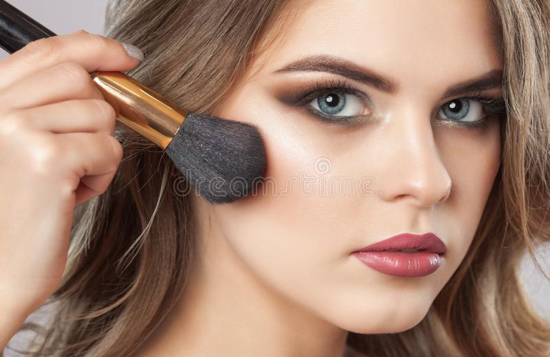 Portrait of a beautiful happy woman with long eyelashes, beautiful smoky eyes make-up, thick eyebrows and with clean skin in a royalty free stock image