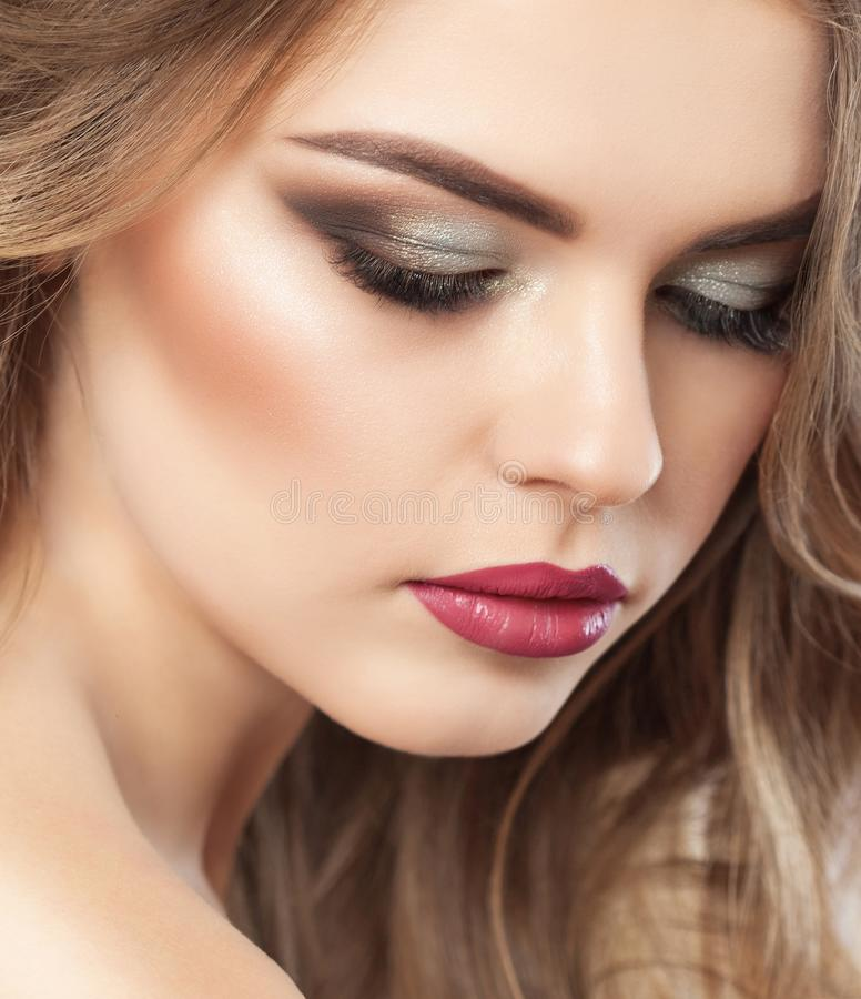 Portrait of a beautiful happy woman with long eyelashes, beautiful smoky eyes make-up, thick eyebrows and with clean skin in a stock photos