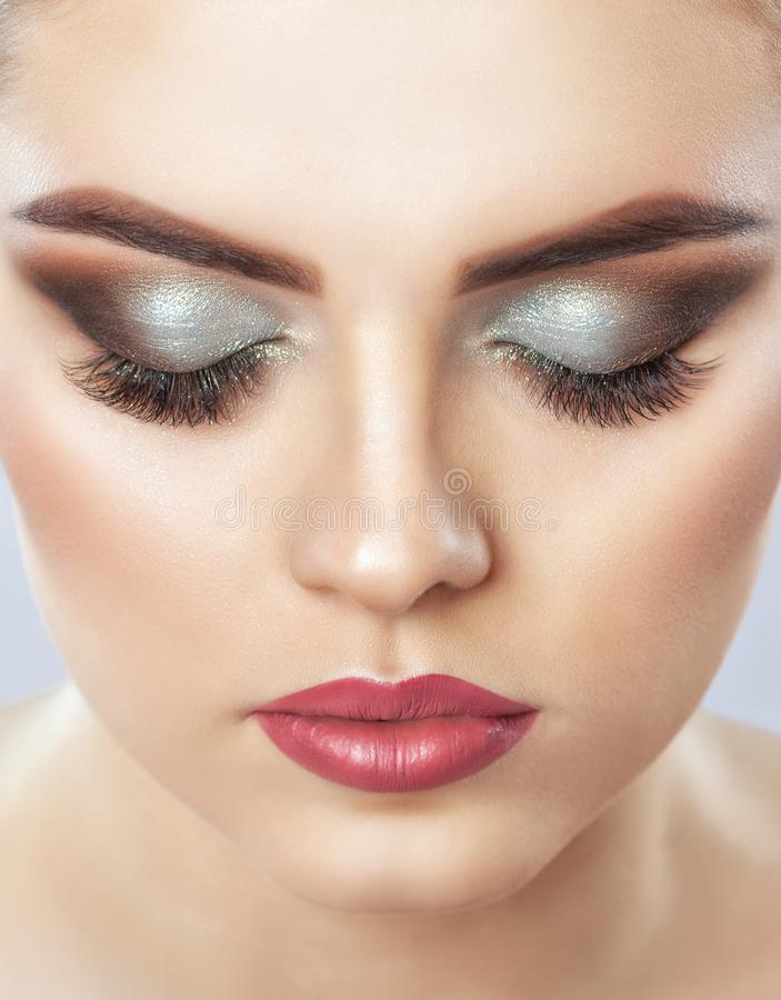 Portrait of a beautiful happy woman with long eyelashes, beautiful smoky eyes make-up, thick eyebrows and with clean skin in a royalty free stock photos