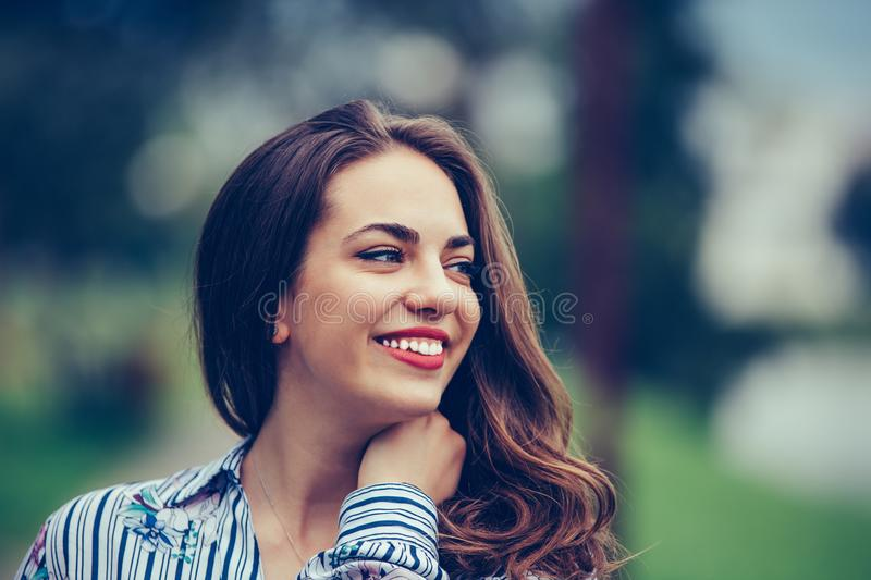Portrait of a beautiful happy woman with a perfect smile outdoors stock photo