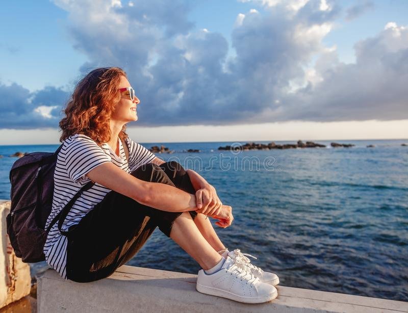 portrait of a beautiful happy young woman sitting on the background of the sea and a beautiful sunset and admiring the scenery stock photos