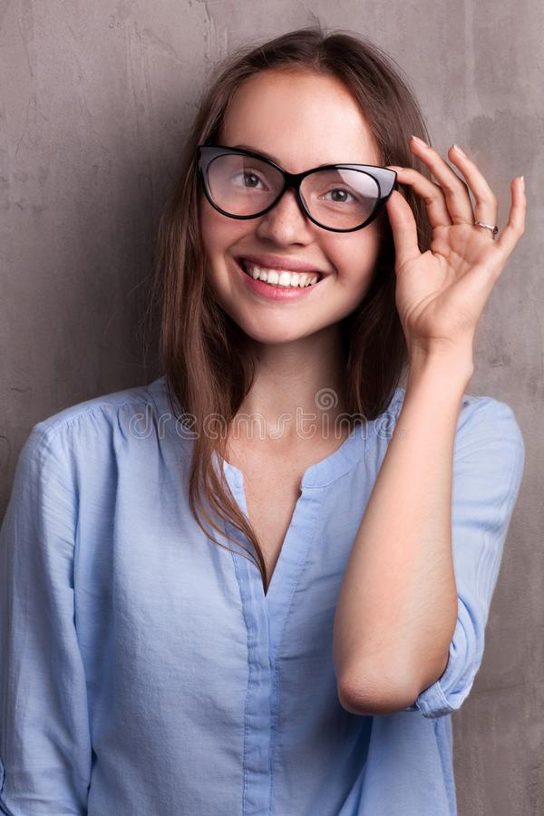 Portrait of beautiful happy young woman wearing glasses near grey grunge wall royalty free stock photo