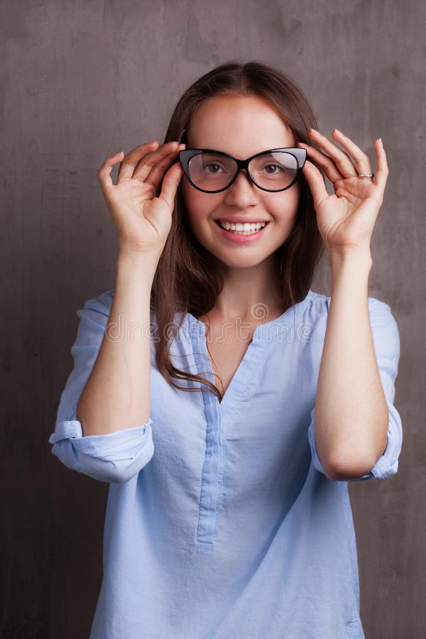 Portrait of beautiful happy young woman wearing glasses near grey grunge wall royalty free stock image