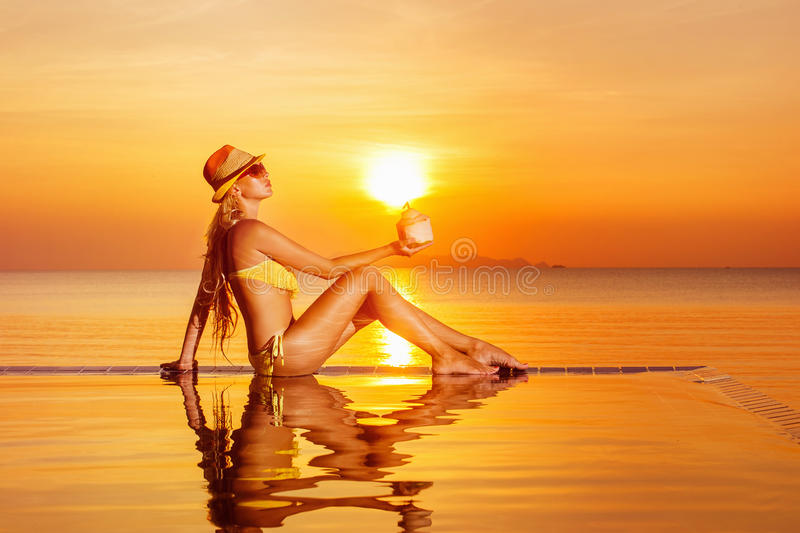 Portrait of beautiful healthy woman relaxing at swimming pool. With coconut in hand at golden sea sunset background royalty free stock photos