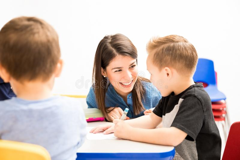 Happy teacher helping one of her students royalty free stock images