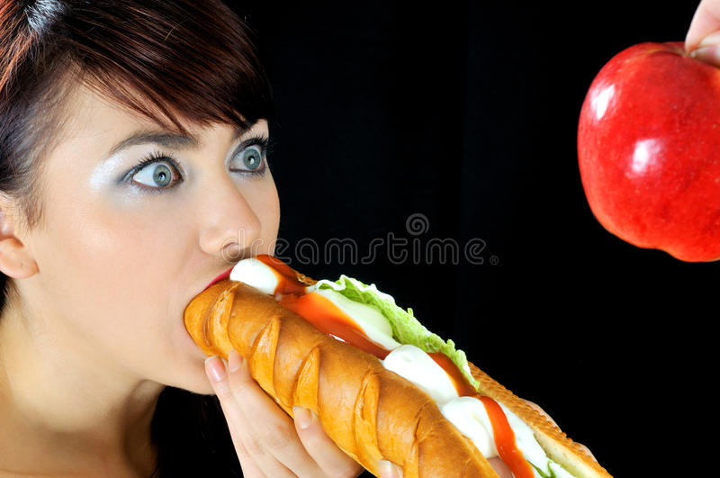 Portrait of beautiful hungry girl eating sandwich royalty free stock image