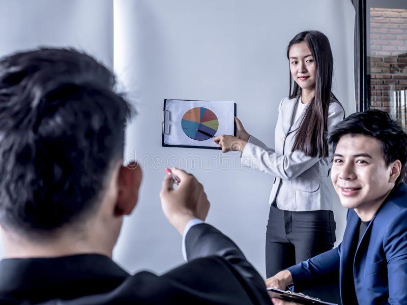 Portrait of beautiful intern standing at office in front of flip chart and presenting with team training flipchart office stock photography