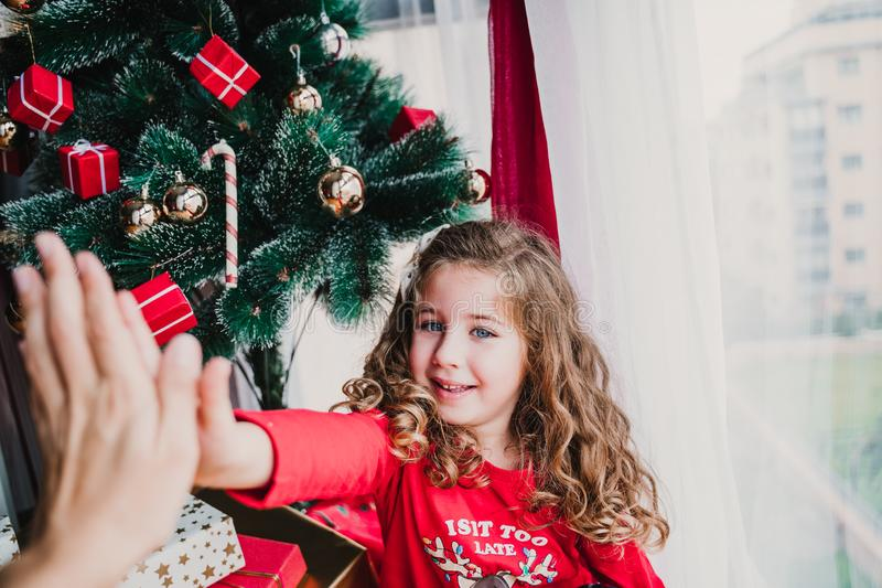 portrait of beautiful kid girl at home by the christmas tree. happy girl doing high five royalty free stock images