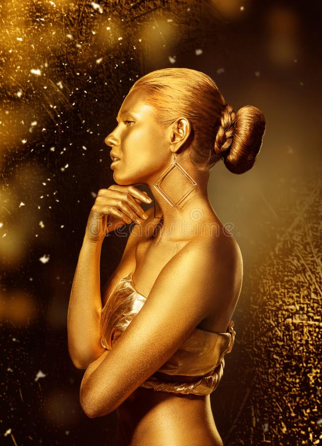 Portrait of beautiful lady with gold paint on skin stock photo