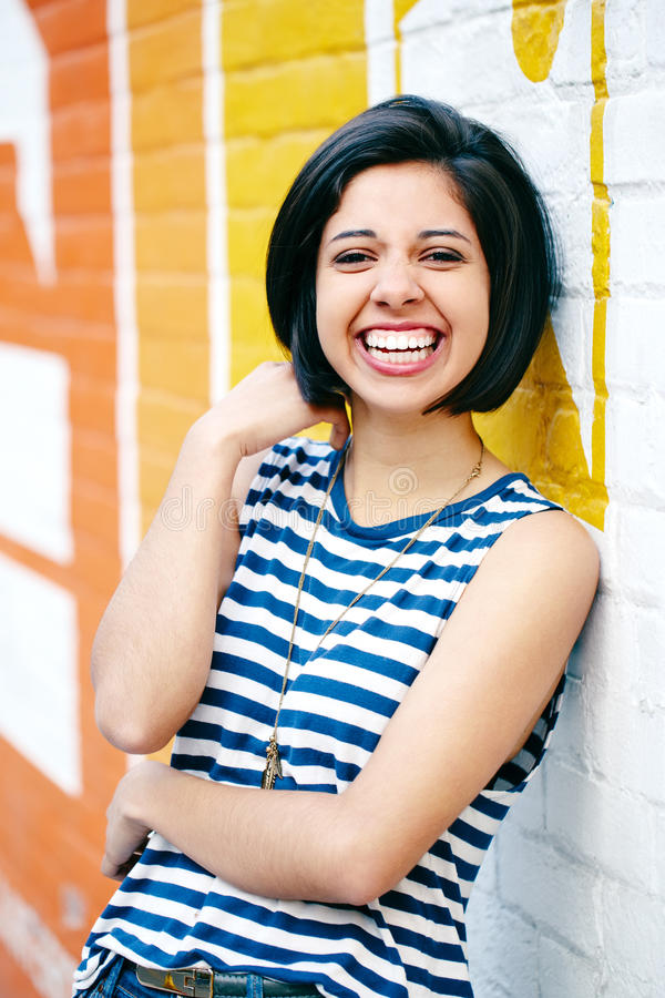 Portrait of beautiful laughing young hipster brunette latin hispanic girl woman with short hair bob. In blue jeans, striped tshirt, leaning on brick wall in royalty free stock images