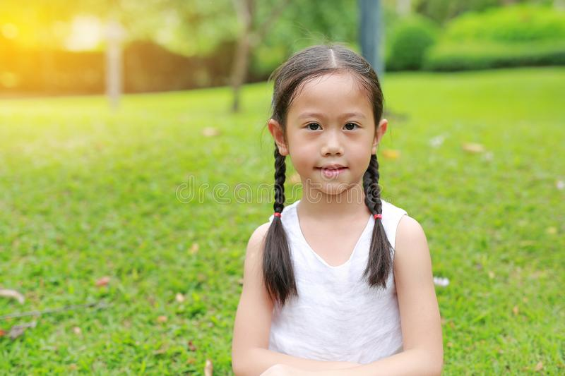 Portrait of beautiful little Asian child girl with two ponytail hair in the garden with morning sunlight stock photos