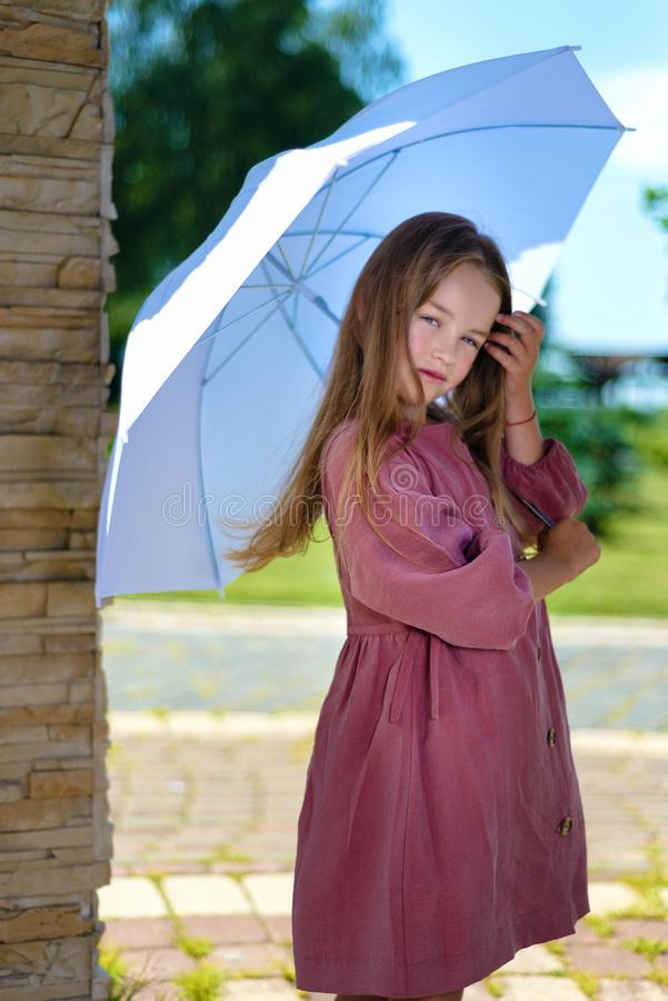 Portrait of beautiful little girl. child in burgundy dress holds an umbrella over his head in bright sunny day royalty free stock photography