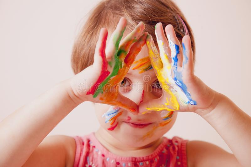 Portrait of beautiful little girl with colorful painted hands and face stock photos