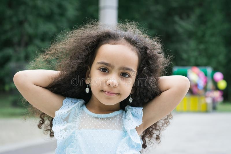Portrait of a beautiful little girl of Egyptian age five years old in a city park on the background of green trees stock images