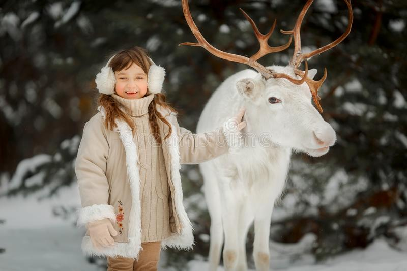Portrait of beautiful Little girl in fur coat at winter forest stock images