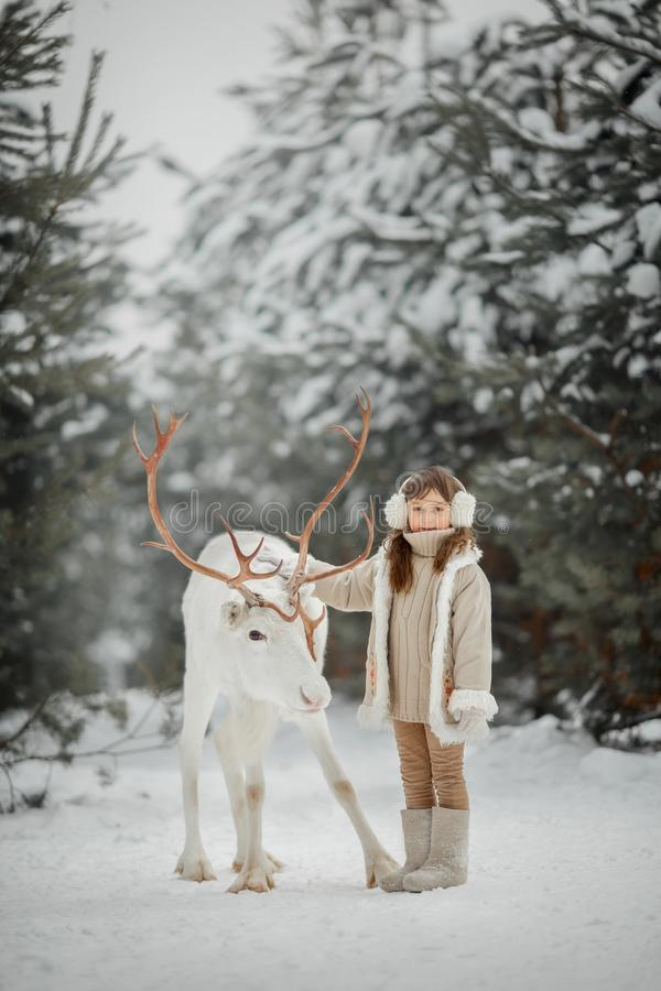 Portrait of beautiful Little girl in fur coat at winter forest royalty free stock images