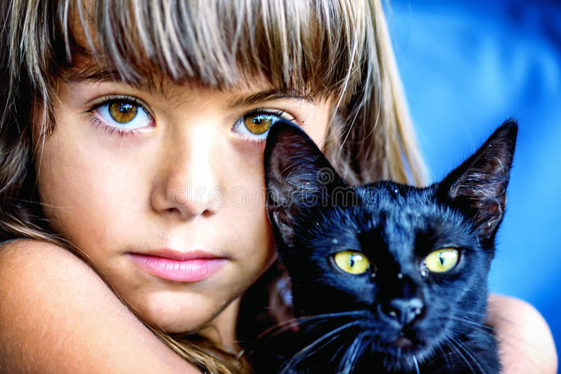Portrait of a beautiful little girl holding a black cat. With yellow eyes royalty free stock photos