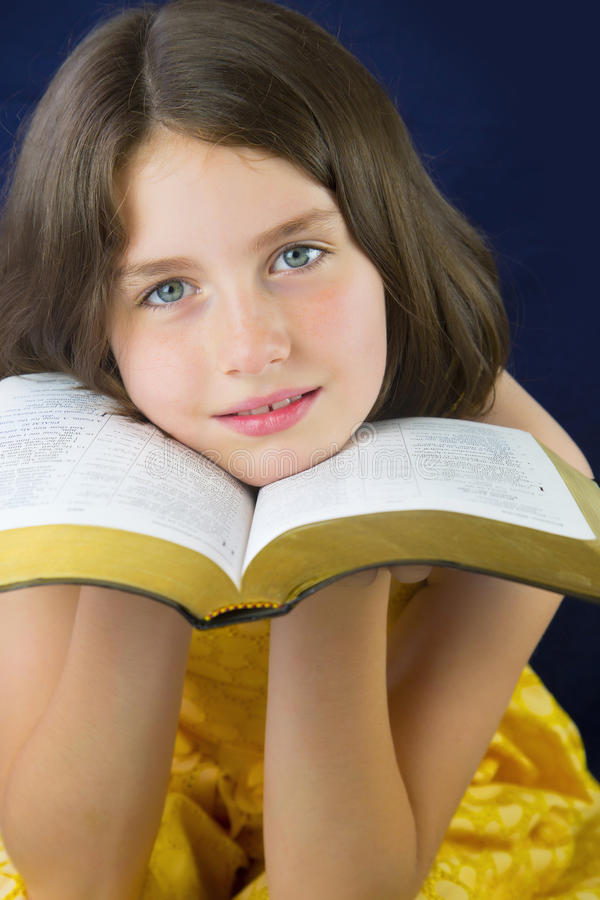 Portrait of beautiful little girl holding Holy Bible royalty free stock photos