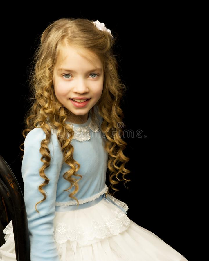 Portrait of a little girl sitting on an old Viennese chair, blac stock photos