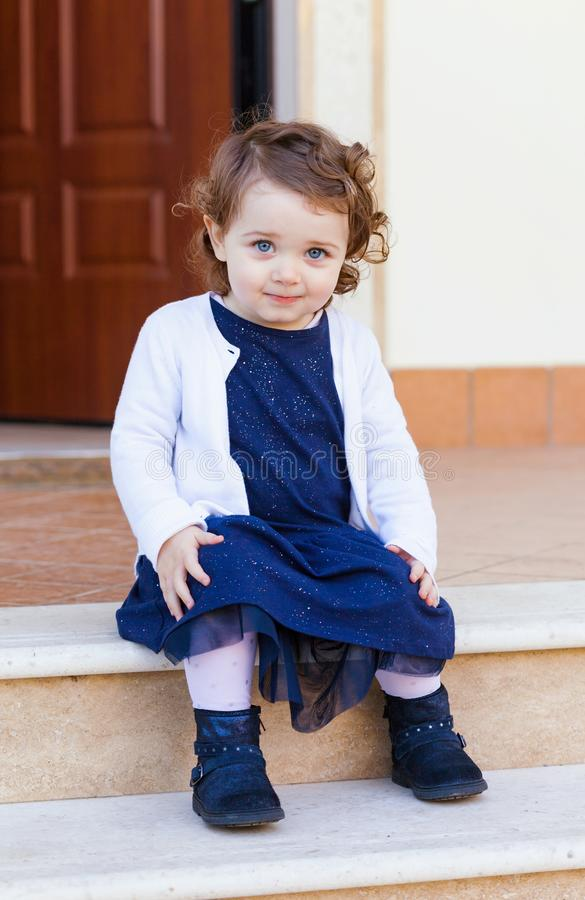 Portrait of a beautiful little girl sitting on the stairs royalty free stock photos